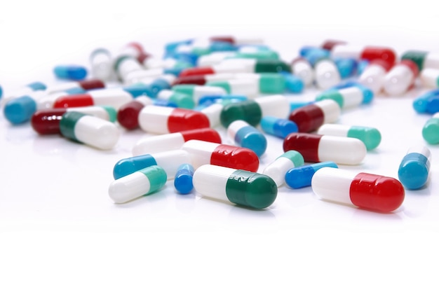 Medische pillen in rood, blauw, groen en andere kleuren. losse tabletten op wit oppervlak. gezondheid en geneeskunde.