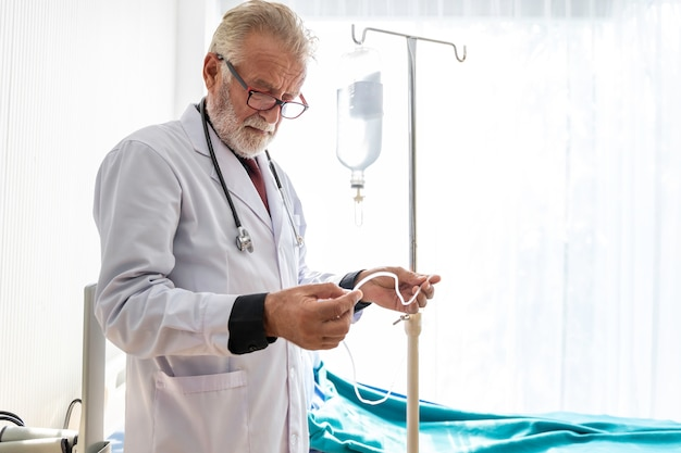 Medische professionals kaukasische senior man zoutoplossing niveaus aan te passen om patiënten te behandelen.