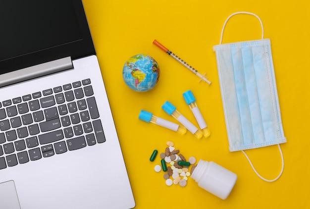 Medische reageerbuizen, gezichtsmasker met spuit, globe en laptop op gele achtergrond. wereldwijde gezondheidszorg. bovenaanzicht
