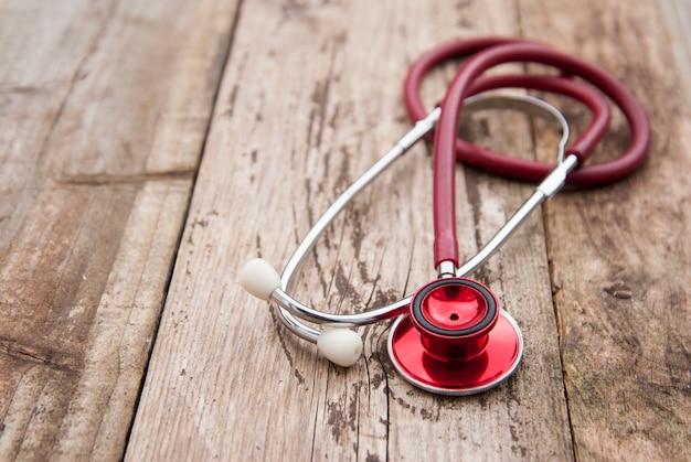 Medische rode stethoscoop die op rustieke houten wordt geïsoleerd. copyspace. gezondheidszorg en medicijnen.