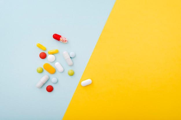 Medische samenstelling. sommige kleur pillen op blauw gele achtergrond, bovenaanzicht. aantal capsules, medicijnen.