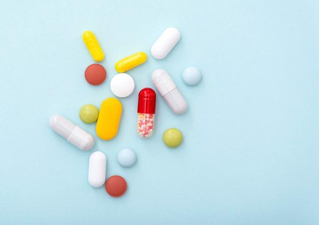Medische samenstelling. sommige kleurpillen op blauwe achtergrond, bovenaanzicht. gele, blauwe, groene, rode, witte capsules, medicijnen.