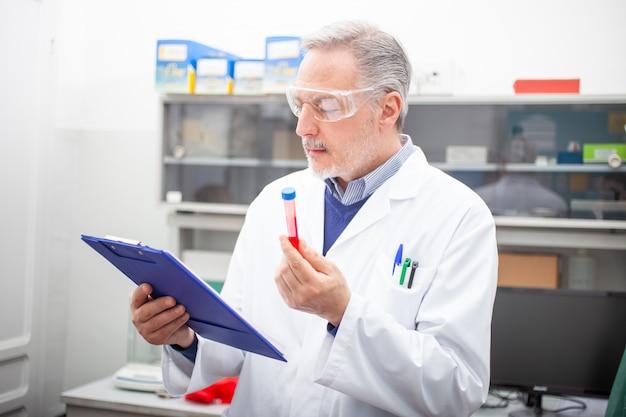 Medische sientistonderzoeker die een bloedbuis, coronavirusbloedtest bekijkt