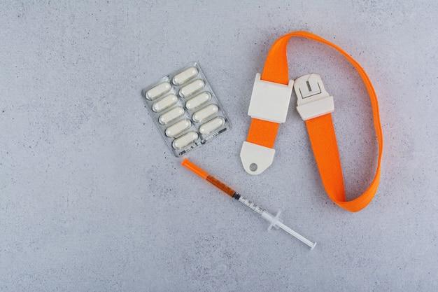 Medische spuit en tabletten op marmeren achtergrond.
