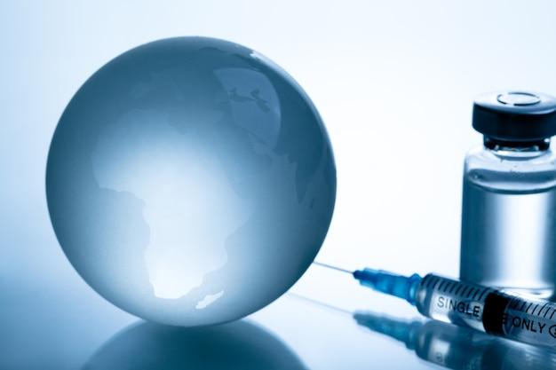 Medische spuit met een naald en een bollte met vaccin op wereldkaart.