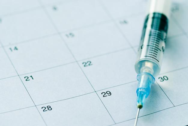 Medische spuit op kalenderachtergrond