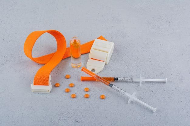 Medische spuiten, ampul en tabletten op marmeren achtergrond.