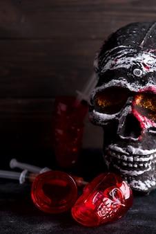 Medische spuiten met tomatensap en een menselijk skeletgezicht als kop op zwarte