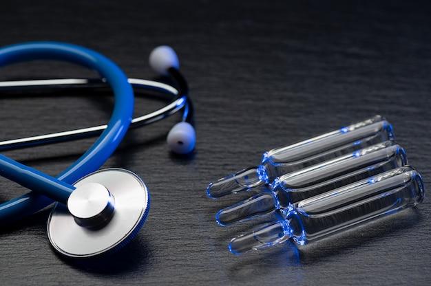 Medische stethoscoop en ampullen met een vaccin of medicijn op grijze tafel