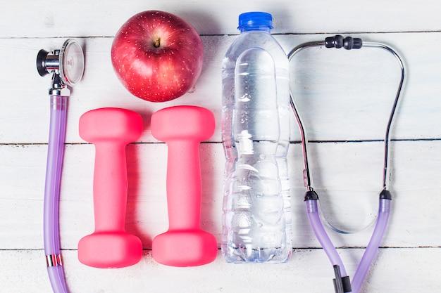 Medische stethoscoop en een appel fruit over houten achtergrond. gezond levensstijl concept beeld.