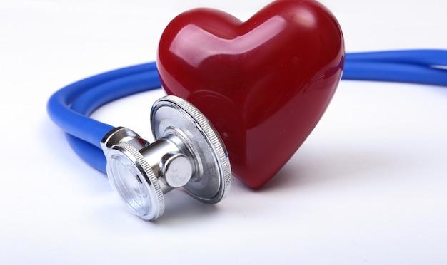 Medische stethoscoop en rood hart dat op wit wordt geïsoleerd