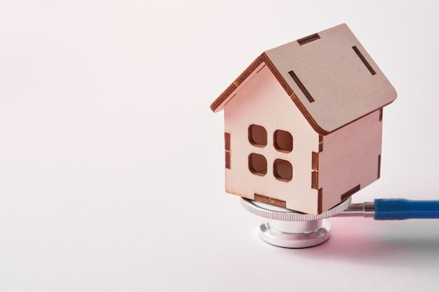 Medische stethoscoop en speelgoed huis op een roze achtergrond met kopie ruimte