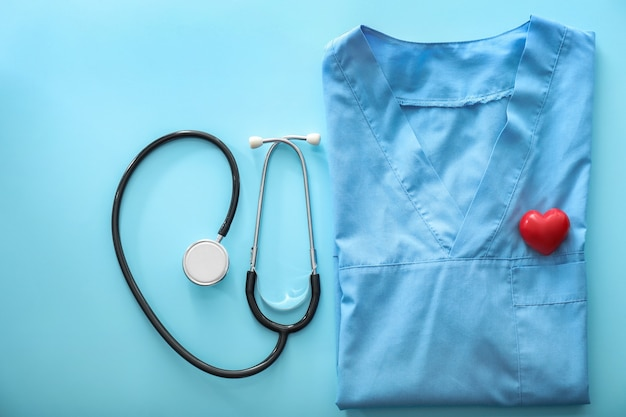 Medische stethoscoop en uniform van arts op kleur. gezondheid concept