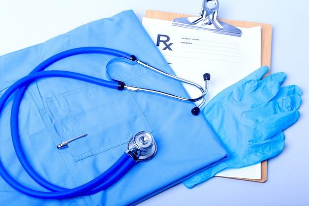 Medische stethoscoop, handschoenen, rx-recept en blauwe arts uniforme close-up.