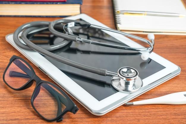Medische stethoscoop voor artsencontrole met tabletcomputer op artsentafel als medisch concept