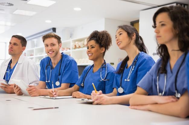 Medische student die bij de camera tijdens klasse glimlacht