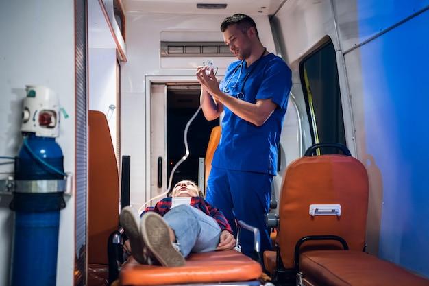 Medische student die een examen heeft, dat voorbereidingen treft om een zuurstofmasker aan zijn patiënt in een ziekenwagenauto te geven