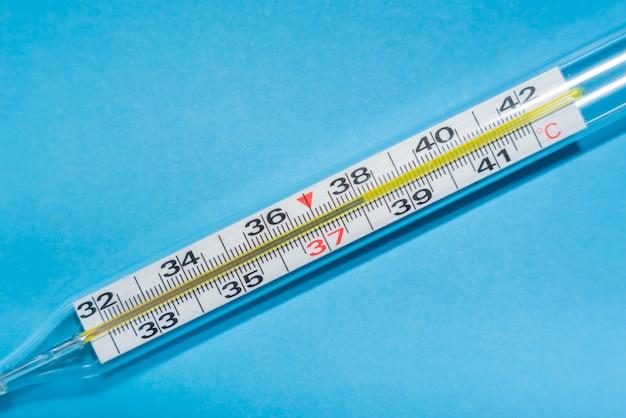 Medische thermometer op een blauw geïsoleerde achtergrond met een temperatuur van 38 graden. verhoogde lichaamstemperatuur van een zieke. het concept van ziekte en slechte gezondheid. kopieer ruimte
