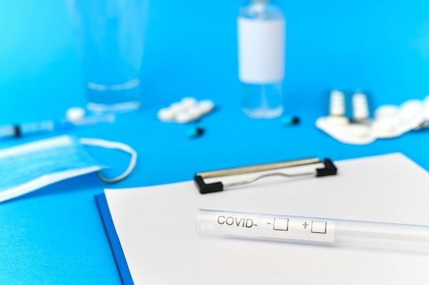 Medische uitrustingen, blocnote en covid-testsamenstelling op blauw oppervlak. bovenaanzicht