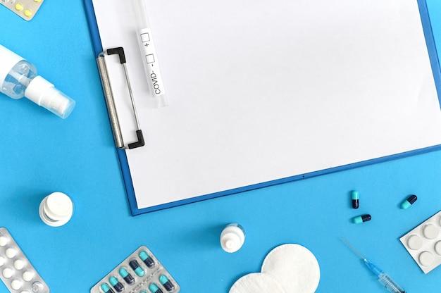 Medische uitrustingen, blocnote en covid-testsamenstelling op blauwe achtergrond. bovenaanzicht