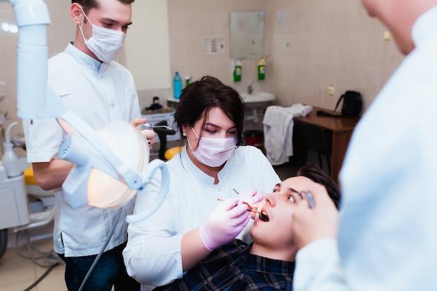 Medische universiteit. professionele leraar tandarts arts behandelt tanden aan de patiënt op kantoor op moderne apparatuur. het concept van medische opleiding en overdracht van ervaring.