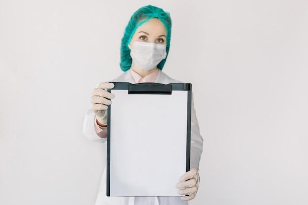 Medische vrouwelijke specialist, arts of verpleegkundige, het dragen van medische pet en masker, met het klembord met blanco papier naar de camera, geïsoleerd op wit, kopieer ruimte. geneeskunde, dokter, gezondheidszorg