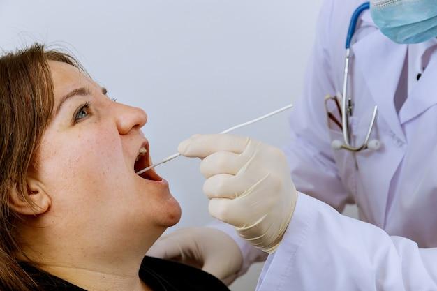 Medische werker in beschermende handschoenen om vrouw op monduitstrijkje in te checken voor pcr-test coronavirus voor covid-19