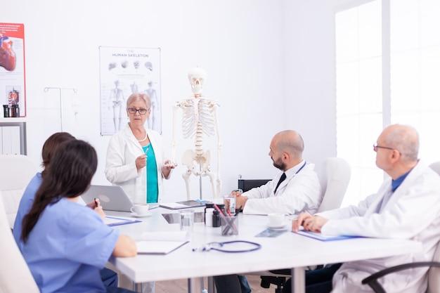 Medische wetenschapper doet demonstratie met menselijk skelet in vergaderruimte met haar team. kliniekdeskundige therapeut in gesprek met collega's over ziekte, medisch professional