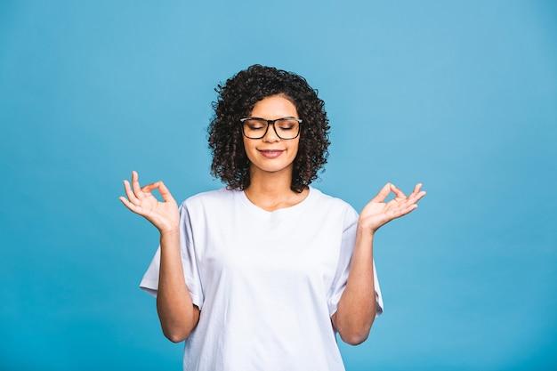 Meditatie concept. mooie jonge afro-amerikaanse vrouw staat in meditatieve houding, geniet van een rustige sfeer, houdt de handen in gebed gebaar, geïsoleerd op blauwe achtergrond.