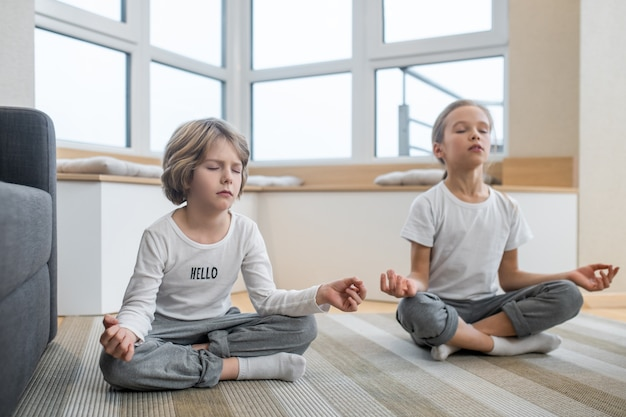 Meditatie. kinderen die thuis samen yoga doen en in meditatie zitten