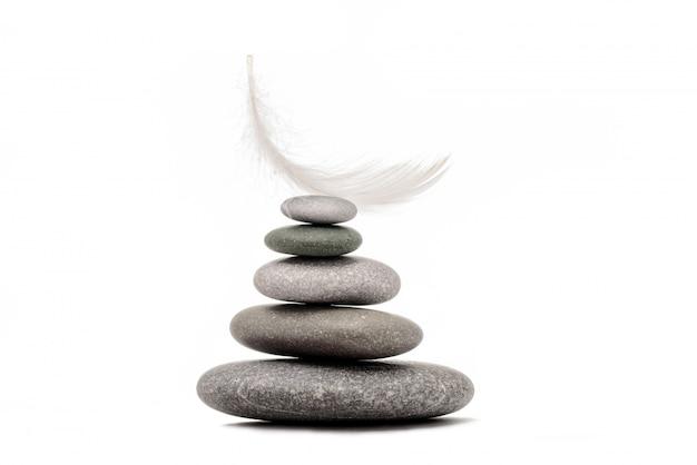 Meditatiestenen en pluim op witte achtergrond worden geïsoleerd die. concept van zwaar en licht.