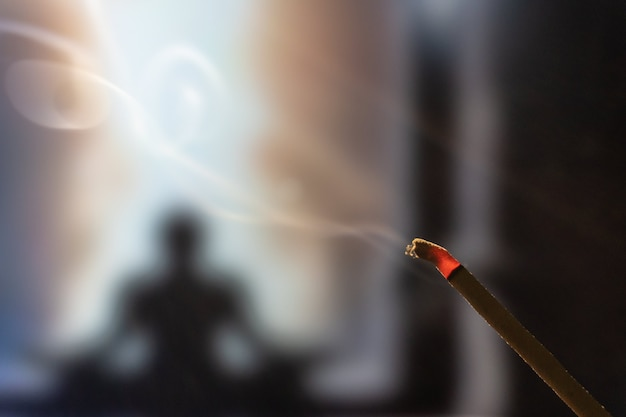 Mediteren in lotushouding. focus op wierookstokje en rook. onherkenbare yogabeoefenaar in de.