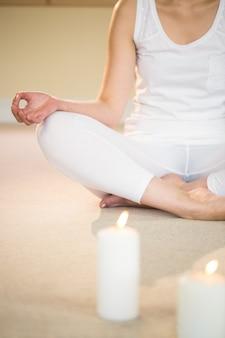 Mediterende vrouw met verlichte kaarsen