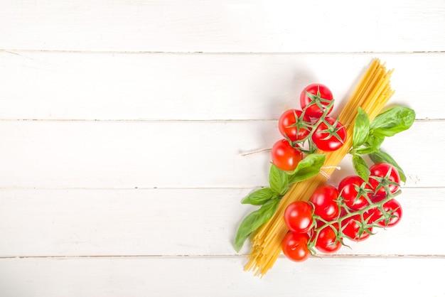 Mediterraan voedsel, de italiaanse kokende ingrediënten van de pastaspaghetti, op de witte houten achtergrond van de keukentafel