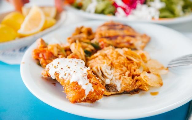 Mediterraan voedselconcept gebakken vis op de witte plaat