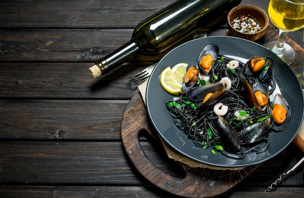 Mediterraans eten. spaghetti met inktvisinkt, tweekleppige schelpdieren en witte wijn op een rustieke tafel.