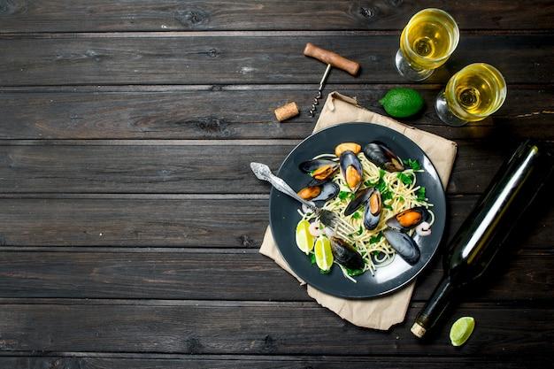 Mediterraans eten. zeevruchtenspaghetti met tweekleppige schelpdieren en witte wijn op een rustieke tafel.