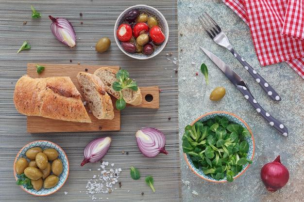 Mediterrane hapjes set. groene en zwarte olijven, brood van vers meergranenbrood, veldsla en rode ui over oude houten achtergrond. bovenaanzicht met ruimte voor tekst