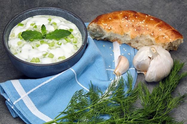 Mediterrane keuken. tzatziki-saus gemaakt van verse komkommers, munt en yoghurt met citroen en knoflook in een donkere kom op een betonnen tafel