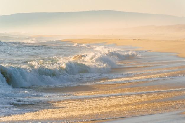 Mediterrane kosten bij zonsondergang. tropische eilandkust met sterke stormachtige golven in beweging. zonlicht op geel zand voorbij oceaan. paradijs schilderachtig zeegezicht.