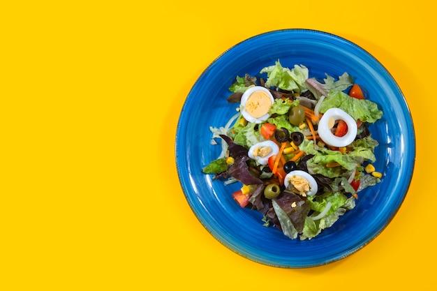 Mediterrane salade die van bovenaf op geel wordt gezien