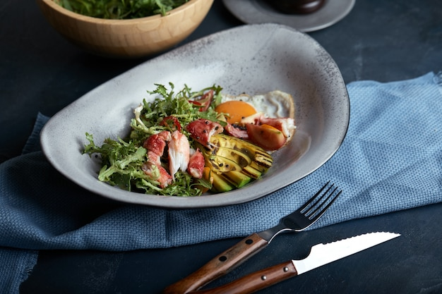 Mediterrane salade met gegrilde krab, kerstomaten, rucola, greens, avocado, limoen, olijven, balsamico saus