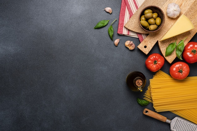 Mediterrane voedselachtergrond met rode tomaten spaghetti olijven basilicum olijfolie knoflook