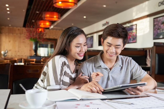 Mediu van aziatisch paar wordt geschoten die datum in coffeeshop hebben die