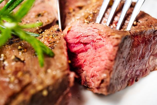 Medium achterste biefstuk. witte plaat met stuk van biefstuk op vork.
