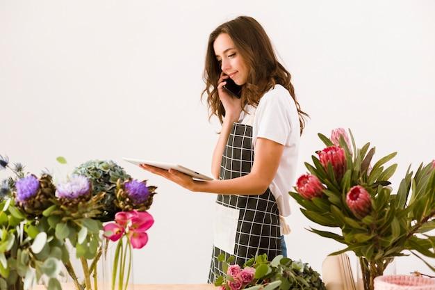 Medium geschoten bloemist met smartphone en tablet