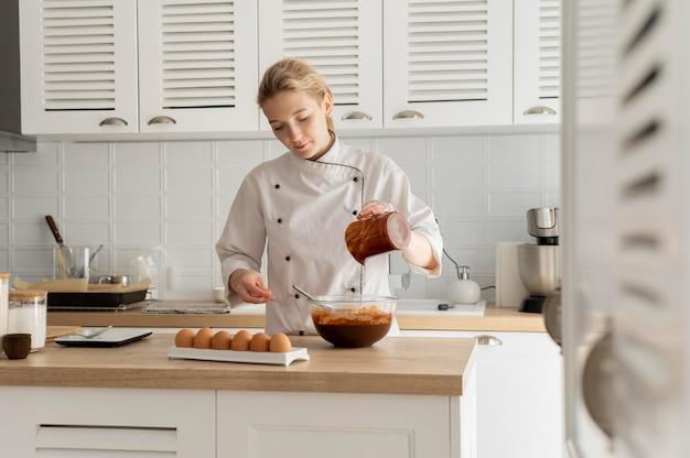 Medium geschoten chef-kok koken in de keuken