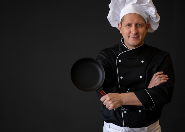 Medium geschoten chef-kok met pan poseren