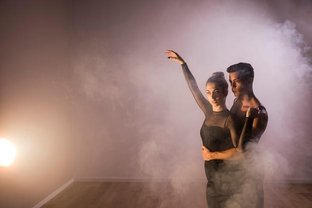 Medium geschoten dansers koppelen elkaar in rook