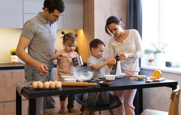 Medium geschoten gezin dat eten klaarmaakt